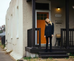 A house with a red door and a happy woman standing outside in a sweatshirt
