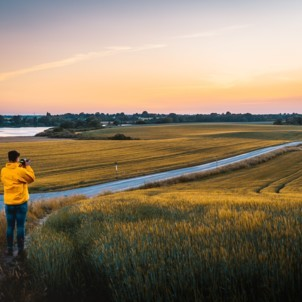 man in a yellow coat taking a picture of the picturesque land