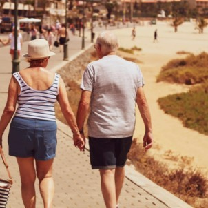 an elderly couple holding hands and touring around a new city