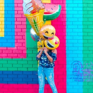 A girl wearing colorful clothing holding a bunch of colorful fun looking emoji baloons